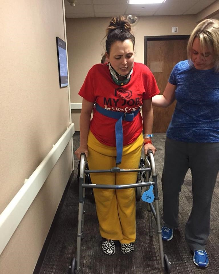 woman with pained face using walker during rehab