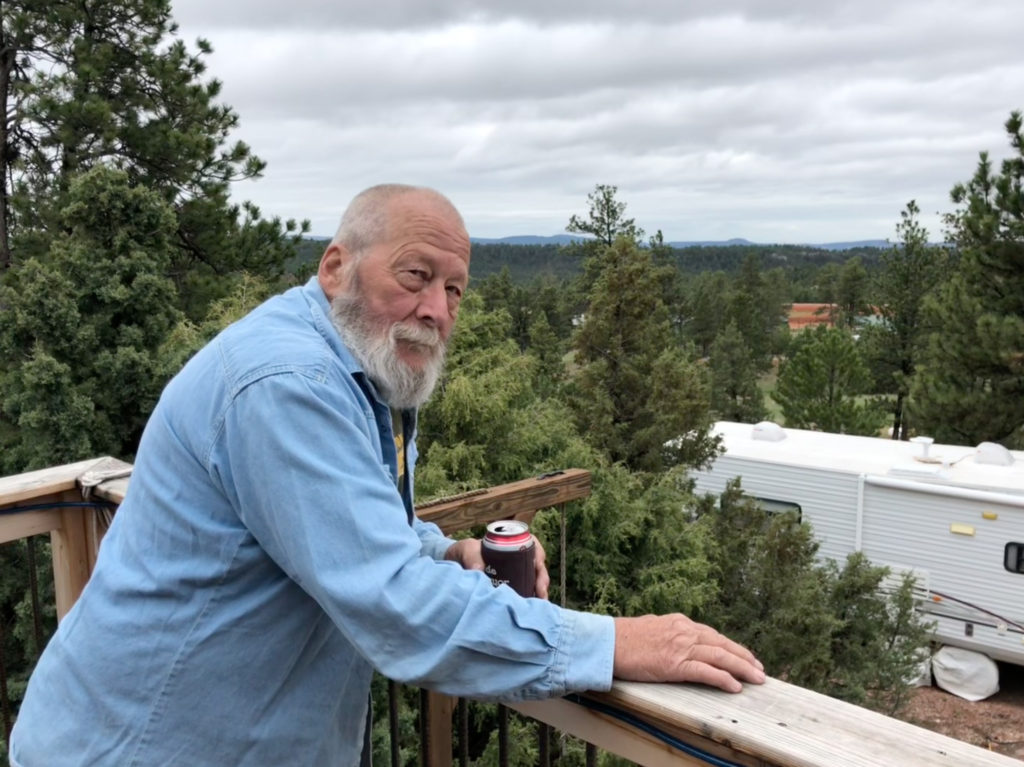 Karl Van Rump on porch overlooking compound in trees.